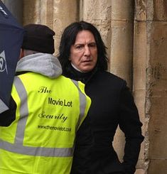 """Alan Rickman behind the scenes as Snape during the filming of """"Harry Potter and the Half-Blood Prince"""", at Gloucester Cathedral with security, 7th February 2008"""