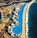 The world's largest outdoor swimming pool is at resort San Alfonso Del Mar in Algarobo, Chile. This pool is registered in the Guinness book of world records. This pool is actually a man made salt water lagoon.  Reportedly causing no damage to the sea, the pool uses a computer controlled suction and filtration system to keep fresh water in constant circulation, drawing it in from the ocean at one end and returning it to the ocean at the other.