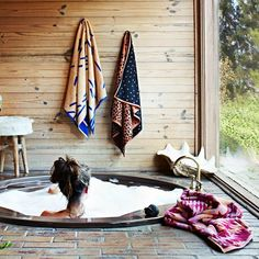 love this dreamboat bath tub next to that large window.