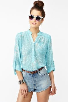 Loose fitting stellar sky blue chiffon blouse featuring a star print and chest pocket with button closures at front the front and tabbed sleeves for easy rolling.
