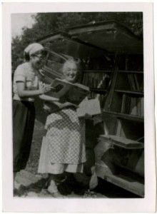 April 13, 2011 ~ In celebration of National Bookmobile Day, a flashback photo of the Watauga County Library bookmobile in Sands, rear view with librarian and library board member laughing and looking at book, 1949. ^cs