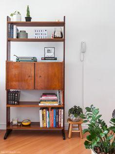 Armário de madeira vintage acomoda livros, plantas e objetos.