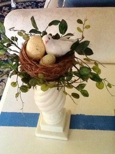 "Beautiful white ceramic candlestick with natural twig nest sits on top with a sweet white bird and egg. Silk greenery surrounds the nest. This chunky candlestick measures 14"" in height and 5"" in diameter. Lovely decorative candlestick for mom, grandma or a special friend.  Thank you for shopping at Bless My Nest and enjoy feathering your nest."