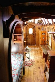 A sleeping nook with a curved opening is part of the detailed woodwork found in the Old Time Caravan. A one-of-a-kind tiny house with a curved roof, round windows, live edge maple desk, mahogany storage staircase, and intricate woodwork throughout. Tiny House Living, Small Living, Bus Living, Living Room, Tiny House 2 Bedroom, Bedroom Small, Kitchen Living, Sleeping Nook, Bed Nook