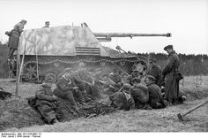 "A German ""Rhino"" anti- tank gun crew sits with fellow infantrymen for a quick meal. 1944."