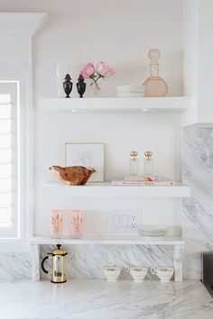 Meredith Heron - Beautiful kitchen features stacked white floating shelves with lighting filled with pink accents atop white and gray marble countertop.