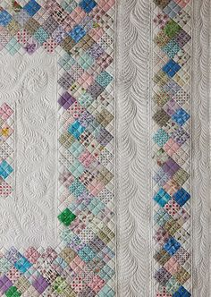 Patchwork quilt with meandering Amish feathered vine quilting by Sue Garman.