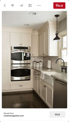 Oil rubbed bronze finishes with white cabinets and stainless steel appliances