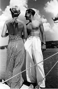Couple standing on a sailboat, she in halter-top beach pajama, he in white trousers, c.1930s.