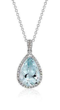 This gemstone and diamond pendant features a light blue pear shape aquamarine framed with a halo of brilliant round diamonds.