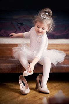 Little girl in pink tutu, trying on her mother's shoes
