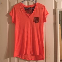 Cute Aztec Pocket Shirt! Worn a handful amount of times. Cute tribal print pocket on the front! The color is coral mixed with orange. Really cute and comfy! Sorry, I don't trade. Rue 21 Tops Blouses