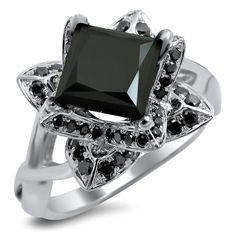 A blooming lotus flower design houses a large black diamond in the center prong setting. Crafted of 14-karat white gold, this engagement ring features a high polish finish and dozens of black side dia