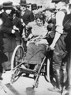 """Rosa May Billinghurst 1876-1953. Rosa May (known as """"May"""") gained prominence through her activities as a suffragette. At 5 months old, Rosa suffered an illness that left her whole body paralyzed.n the last big suffragette demonstration before the outbreak of World War One, May projected her tricycle towards the line of mounted policemen. After that, she chained her tricycle to the railings outside Buckingham Palace"""