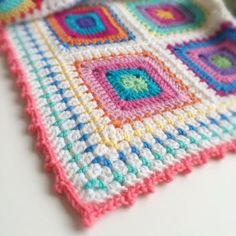 Festiva Blanket, free pattern by Michelle Robinson of Poppy & Bliss. Solid blocks with chain round & white border, join as you go. Block stitch border with picot edging.