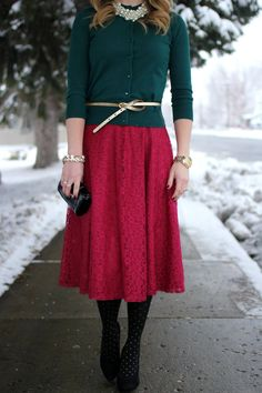Red lace midi skirt, green sweater, gold belt, black polka dot tights and heels