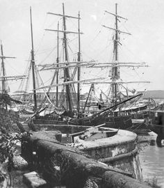 Sailing ships on the Pasig River next to Fort Santiago, Manila, Philippines, late 19th Century.