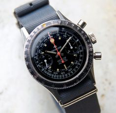 A gorgeous example of an original rare Chronosport chronograph from the 60s. Original features include: black dial with orange patina on the indexes; chronograph to calculate average speed, convert between speed units, and perform all critical calculations required while flying; manual movement with 18,000 bph, 17 jewels, caliber Valjoux 7733, 38mm case. We have replaced the strap with a grey NATO strap. This handsome vintage watch runs very well, holds a good charge and keeps … Read More →