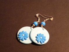 Orecchini con margheritona blu su fondo azzurro.