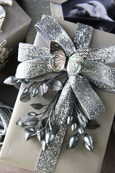 Create a beautiful silver embellishment for a gift by making a bow with metallic ribbon and spray painting small artificial flowers or berries. #gift wrapping #silver