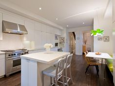 Featured in a traditional townhouse, this kitchen was given a contemporary edge with white walls and cabinets, a sleek kitchen island with silver chairs, and a breakfast nook with a basic white table and creative green chandelier.