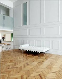 wood herringbone floors, pale grey paneled wall, contemporary furnishings, modern mix