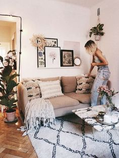 Boho living room with white shaggy rug, beige comfy couch, throw pillows, potted indoor plants, string lights, framed prints on collage wall