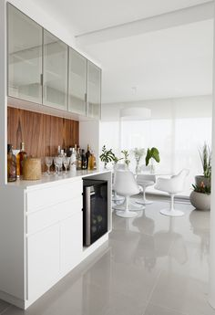 A Sala de Jantar e área de bar foram integradas à varanda do apartamento clean e minimalista. Piso de porcelanato cinza, marcenaria laqueada branca com pau ferro e mesa oval de pedra Saarinen.