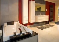 This contemporary bathroom features a Villeroy & Boch Squaro bath with filler & whirlpool jet system; Dansani Kantate 1410mm double basin with two-drawer vanity unit in a vibrant matt white finish; & matching Dansani tall cabinets. Above the basin is the Dansani illuminated mirror with hands-free sensor and integrated lights, on a background of Villeroy and Boch Architectura black mosaic wall tiles.   The soft grey floor tiles help to highlight the monochrome features of the sanitaryware.