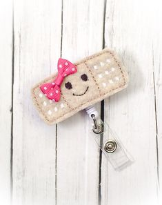 Retractable Badge with a cute happy face Band-Aid made with tan sturdy, comes with a Cute Bow and matching rhinestone on snap. If you wish