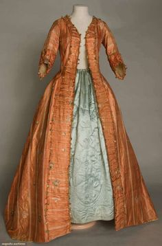 BROCADE SACK BACK OPEN ROBE, 1765-1775, Shrimp silk, narrow pale ivory stripes brocaded w/ scattered floral baskets & sprigs, elbow length sleeves, self ruched fabric w/ fly fringe edge trims sleeves & dress front opening, multi-color striped silk lining, dull red linen bodice lining w/ 3 CBties, sleeve linings in ivory & navy wide striped linen homespun, 2 side slits in skirt. Augusta Auctions