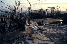A girl does her homework on a rooftop in the Kowloon Walled City (KWC), which was a densely populated settlement in Kowloon City, Hong Kong UrbanHell Kowloon Walled City, Hong Kong, British Journal Of Photography, Candid Photography, High Rise Building, World Images, Do Homework, Lost City, Slums