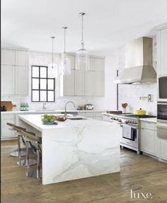 so much to love in this kitchen...the steel window, the incredible marble waterfall island, the glass pendant lighting