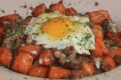 SWEET POTATO POUTINE  Our sweet potato tater tots fried and topped with queso cheese, ground Italian sausage and topped with fried egg.