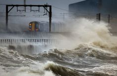 A train passes along the coast along Saltcoats, Scotland, as Britain is braced for the worst as a combination of high tides, heavy rains and strong winds were expected to bring more severe flooding to many parts of the country.
