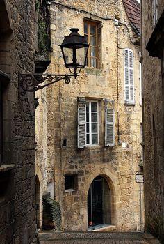 Rue de Sarlat, Sarlat-la-Canéda, Dordogne, France. Sarlat-la-Canéda is a largely-untouched 14th-century village in the Périgord Noir region of France. It is on France's Tentative List for future nomination as a UNESCO World Heritage Site.