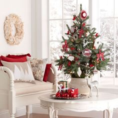 Give traditional Christmas colors a break by removing the green and adding cream and white for a warm and cozy color scheme. Cream and red throw pillows -- with a cream rosette wreath above the chair -- add a warm element to the decor, and a three-foot tabletop tree adorned with red and white ornaments stands in a cream pot on a white table to round out the color scheme.