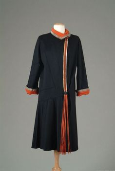 Coat, Poiret, 1924. Black wool lined with red crepe and edged with metallic gold braid and gilded leather. Side closer accented with leather fringe. Black wool with raised stitching on gored skirt, sleeves, and body of coat.