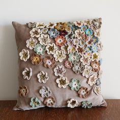 crochet flowers on a cushion, nicely done  ahhh so this is what i can do with all my scrap flowies!!! this or attach to scarf oh the possibilities are endless
