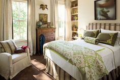 Marsh-Inspired Bedroom - Colorful Coastal Bedrooms - Southernliving. A classic striped headboard and bed skirt are combined with Indian batik-inspired textiles for a sophisticated look. The curtains' woven tape trim adds natural textures, and a photograph of an alligator above the bed is a nod to Louisiana's gator-inhabited marshlands.  View the full home tour.