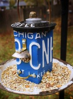 License plate bird feeder....enamel plate, drawer pull, spoon/scoop, coffee canister top....AWESOME~!