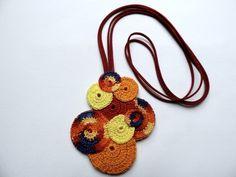 Colar confeccionado em mandalas de crochê com corrente de couro. Feito para ser usado dos dois lados. É enrijecido, colado e costurado com fino acabamento. Cor vermelha, laranja e amarelo.