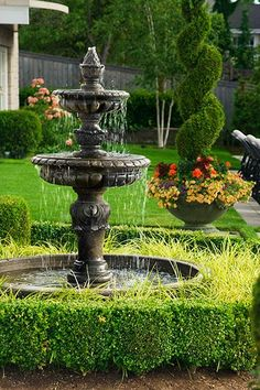 Set among topiary shrubs and sheared hedges, this traditional two-tiered fountain's aged finish underscores the garden's classical feel. Hedges encircling the basin keep children a safe distance from the water.