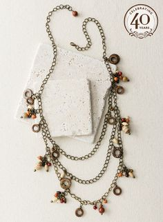 A cascade of 3 bronze chains is strung in a medley of wood rings and soapstone beads.