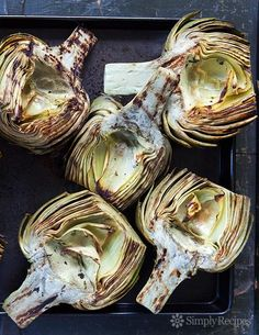 Grilled Artichokes are the BEST! Artichoke halves, steamed first, then infused with herbed oil and grilled until smoky and tender. Delicious! On SimplyRecipes.com