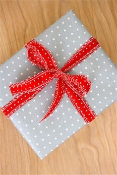 Darling wrapping paper idea with long fabric strip (uses serger here)