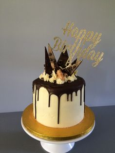 Tiramisu cake - vanilla sponge layers drizzled with rum and espresso syrup, mascarpone buttercream filling, white chocolate buttercream frosting, topped with dark chocolate drip, white chocolate cookies and buttons, chocolate shards and chocolate dipped coffee beans