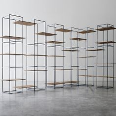 The TT3 bookcase shelves by Ron Gilad are composed of Italian walnut and held together by thin metal frames.