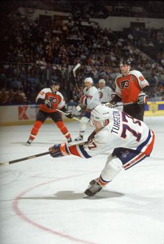 Canadian professional hockey player Pierre Turgeon center for the New York Islanders fires a shot towards the net while his teammates and opposing...