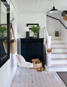 "White entryway—The front hallway, awash in one shade of white, is panelled from the ceiling to the walls to the floor, which homeowner Anna Truelsen and her husband sanded themselves. Black accents ground the space. ""It's one of my favorite colours because it's stylish and adds weight to a white interior,"" she says."